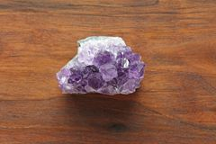 Amethyst stone. Natural Amethyst stones of minerals on a background of natural wood American black walnut. Beautiful untreated st. One and mineral, crystals royalty free stock photo