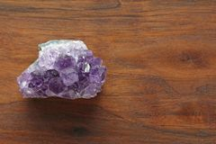 Amethyst stone. Natural Amethyst stones of minerals on a background of natural wood American black walnut. Beautiful untreated. Stone and mineral, crystals stock image