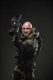 Ametralladora del control del hombre del soldado en un fondo oscuro Foto de archivo libre de regalías