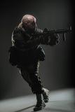 Ametralladora del control del hombre del soldado en un fondo oscuro Imagenes de archivo