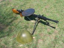 Ametralladora vieja y casco militar en hierba verde Foto de archivo