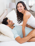 Ami écartant les jambes de brune attrayante sur le lit Photos stock