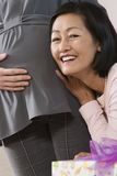 Ami écoutant le ventre de femme enceinte Photo stock