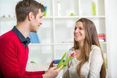 Ami étonnant son amie avec le cadeau, dans le salon Photos libres de droits