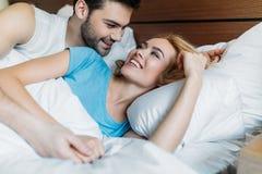 ami étreignant l'amie de sourire dans le lit Photos stock