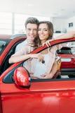 Ami étreignant son amie de la voiture rouge proche arrière dans la salle d'exposition tandis qu'elle se tenant Image libre de droits