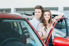 Ami étreignant son amie du dos tout en se tenant près de la voiture rouge Photos stock