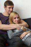 Ami étreignant son amie sur le divan Image stock