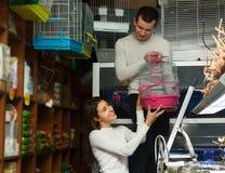 Ami aidant à choisir la cage à oiseaux Image stock