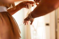 Ami aidant la jeune mariée étant prête pour épouser pendant le matin Photos libres de droits