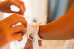 Ami aidant la jeune mariée étant prête pour épouser pendant le matin Photographie stock libre de droits