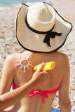 Ami appliquant la lotion de protection solaire au-dessus de la femme bronzage Photo stock