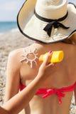 Ami appliquant la lotion de protection solaire au-dessus de la femme bronzage Photographie stock libre de droits