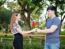 Ami asiatique offrant à son amie par groupe de roses en parc Photo stock