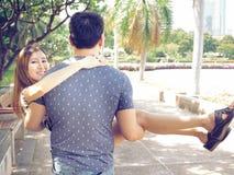 Ami asiatique portant son amie de sourire en parc public Photographie stock