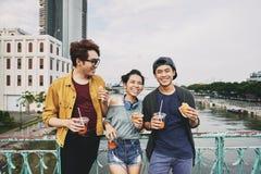Ami asiatique se penchant contre la balustrade de pont Photo stock