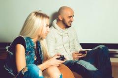 Ami ayant l'amusement et jouant des jeux d'ordinateur avec son girlfri Images stock