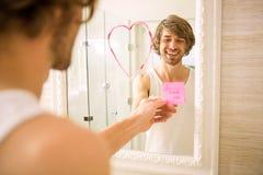 Ami découvrant un message d'amour sur le miroir Images stock