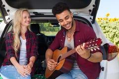 Ami de écoute de jeune fille jouant la campagne extérieure se reposante de tronc de voiture de couples de guitare Photo libre de droits