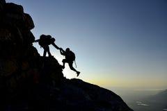 Ami de aide de grimpeur sur le flanc de montagne Photographie stock
