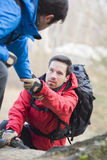 Ami de aide de randonneur masculin tandis que trekking dans la forêt Image libre de droits