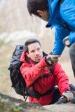 Ami de aide de randonneur masculin tandis que trekking dans la forêt Photo libre de droits
