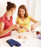 Ami de deux femmes faisant cuire ensemble, ayant l'amusement Photos libres de droits