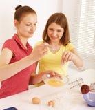 Ami de deux femmes faisant cuire la nourriture ensemble, ayant l'amusement Photographie stock libre de droits