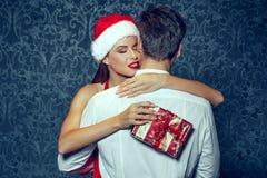 Ami de embrassement de femme de Santa avec surprise de Noël Photographie stock libre de droits