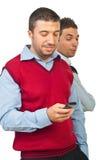 Ami de espionnage d'homme avec le téléphone Photographie stock
