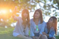Ami de femmes riant et regardant le téléphone portable Image libre de droits