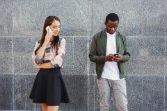 Ami de observation de fille fâchée causant sur le mobile Image stock