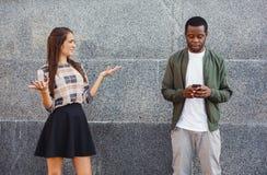 Ami de observation de fille fâchée causant sur le mobile Photos stock