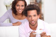 Ami de observation jouant des jeux vidéo Photo stock