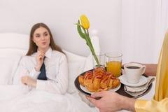 Ami de soin apportant le petit déjeuner dans le lit Images libres de droits