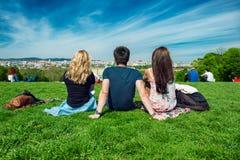 Ami de touristes s'asseyant sur l'herbe verte avec la belle vue au panorama de Vienne Photographie stock