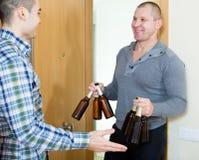 Ami de visite qui a apporté la bière Photos libres de droits