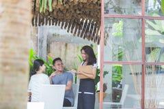 Ami deux en café parlant à la serveuse commandant de la nourriture Images stock