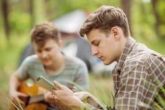 Ami deux s'asseyant dans la tente, jouant la guitare et la lecture Images libres de droits