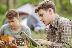 Ami deux s'asseyant dans la tente, jouant la guitare et la lecture Photo stock