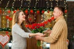 Ami donnant des fleurs à son amie le jour du ` s de Valentine Photos stock