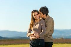 Ami embrassant l'amie sur la joue à l'extérieur. Image libre de droits