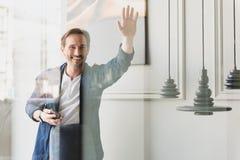 Ami enthousiaste de salutation d'homme d'affaires par la fenêtre Photographie stock