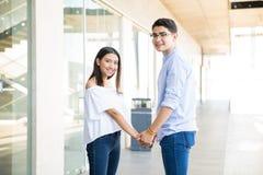 Ami et amie appréciant dans le couloir au centre commercial Image stock