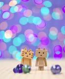 Ami et amie de Danbo Danboard avec le fond coloré de bokeh Image stock
