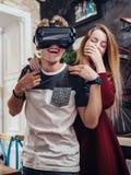 Ami et amie examinant le nouveau casque de vision du vr 3d passant le temps ayant ensemble l'amusement riant à la maison Images libres de droits