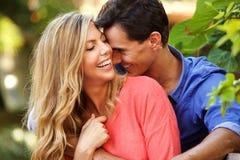 Ami et amie heureux dans l'amour se reposant dehors dans l'étreinte Image stock