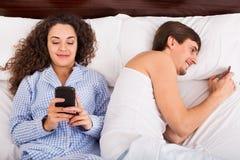 Ami et amie occupés avec des smartphones dans la chambre à coucher Images libres de droits