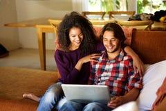 Ami et amie s'asseyant à la maison avec l'ordinateur portable Images stock
