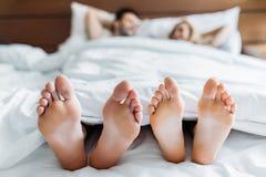 ami et amie se situant dans le lit avec des pieds Photos stock